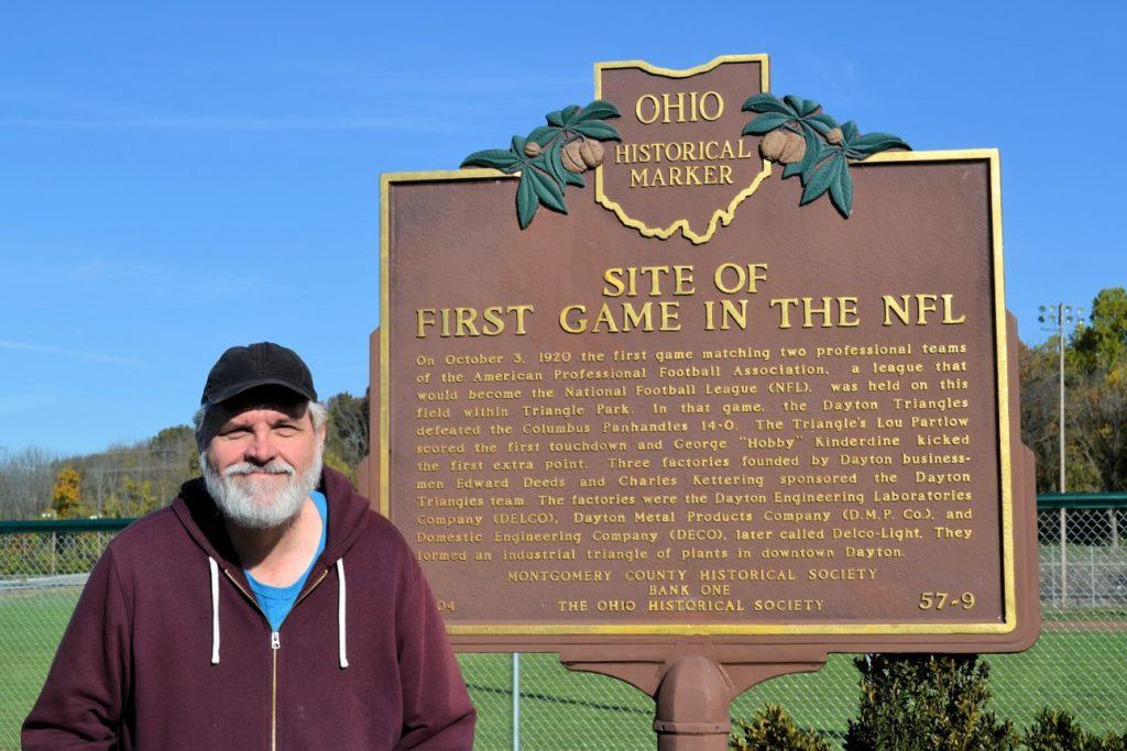Bruce standing beside NFL first game historical marker